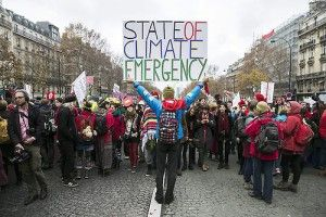 ETI02. Paris (France), 12/12/2015.- A demonstrator holds a poster stating 'State of Climate Emergency' behind indigenous people during a protest as the COP21 reaches its end in Paris, France, 12 December 2015. The 21st Conference of the Parties (COP21) is held in Paris from 30 November to 12 December aimed at reaching an international agreement to limit greenhouse gas emissions and curtail climate change. (Protestas, Francia) EFE/EPA/ETIENNE LAURENT
