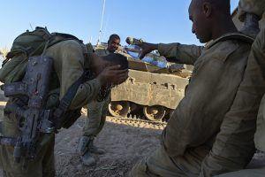 """ISR05. SDEROT (ISRAEL), 21/08/2014.- Un grupo de soldados israelíes descansan junto a un tanque en un lugar sin localizar de la frontera de Israel con la Franja de Gaza hoy, jueves 21 de agosto del 2014. Las """"Brigadas Azedim al Kasem"""", brazo armado de Hamás, prometieron hoy vengar la muerte de tres de sus comandantes, alcanzados esta madrugada por disparos de la aviación de guerra israelí contra un edificio de la ciudad de Rafah, en el sur de Gaza. En un comunicado difundido a través de la página web, la milicia palestina asegura que Israel """"pagará un enorme precio por el asesinato"""" de Muhamad Abu Shamala, Raed al-Attar, Mohamad Barhum y otras cinco personas. EFE/Jim Hollander"""